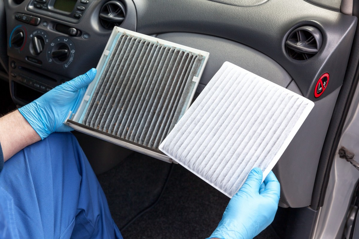 technician holding a clean and dirty air filter comparison in the front seat of a car